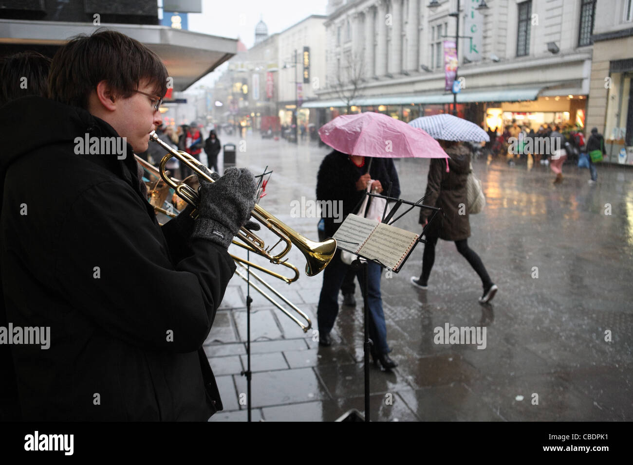Buskers play xmas carols while people with umbrellas walk past in heavy rain Northumberland St, Newcastle. Stock Photo