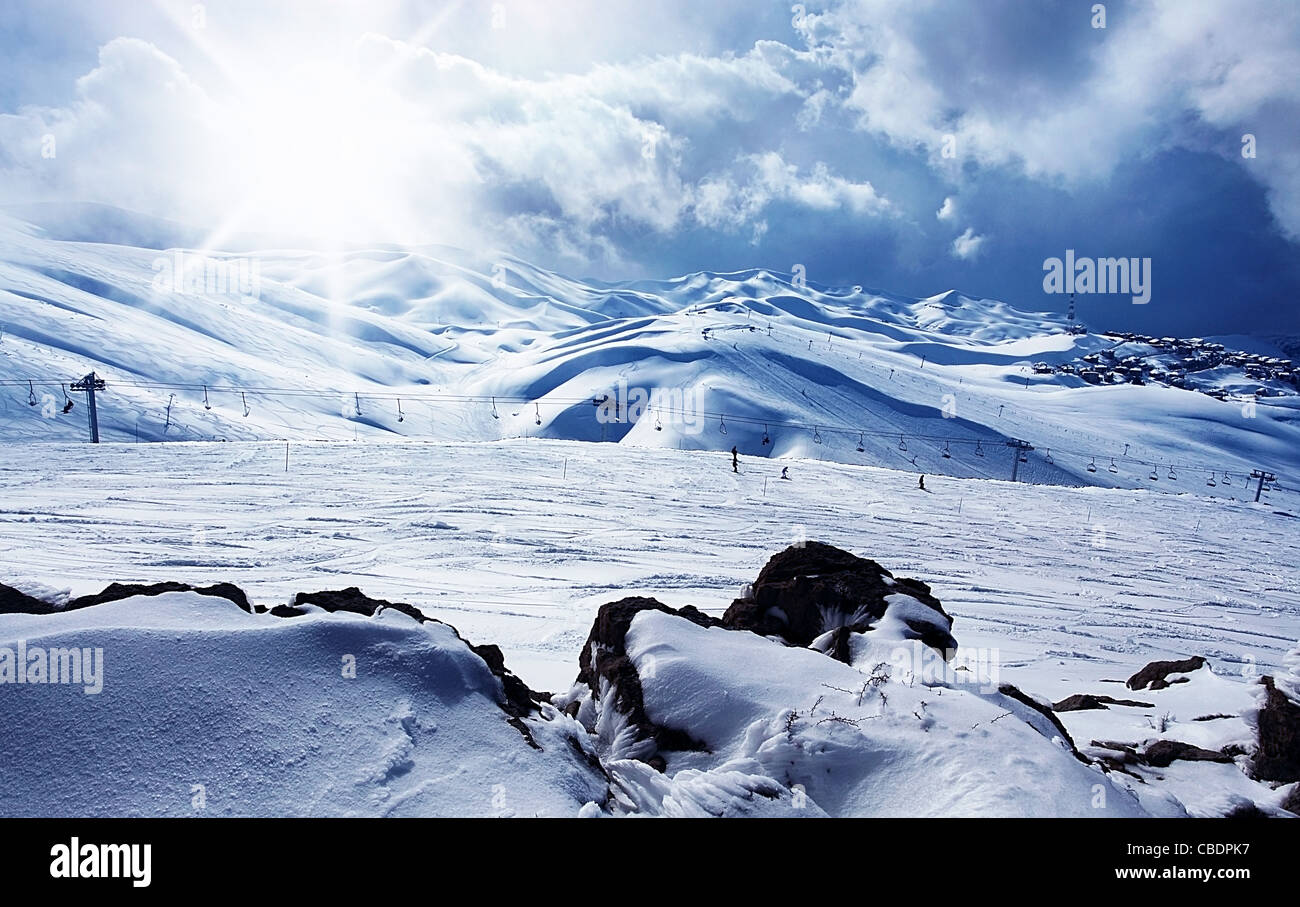 Winter mountain ski resort panoramic landscape with snow, sunny sky & chairlifts Stock Photo