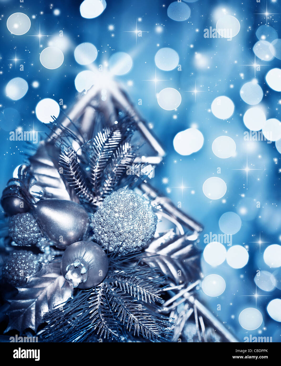 Beautiful silver Christmas tree decoration, blue shiny holiday background with blur bokeh glowing light and glitters Stock Photo