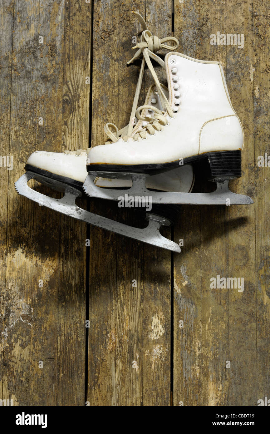 white ice skates hanging on an old weathered wooden wall - Stock Image