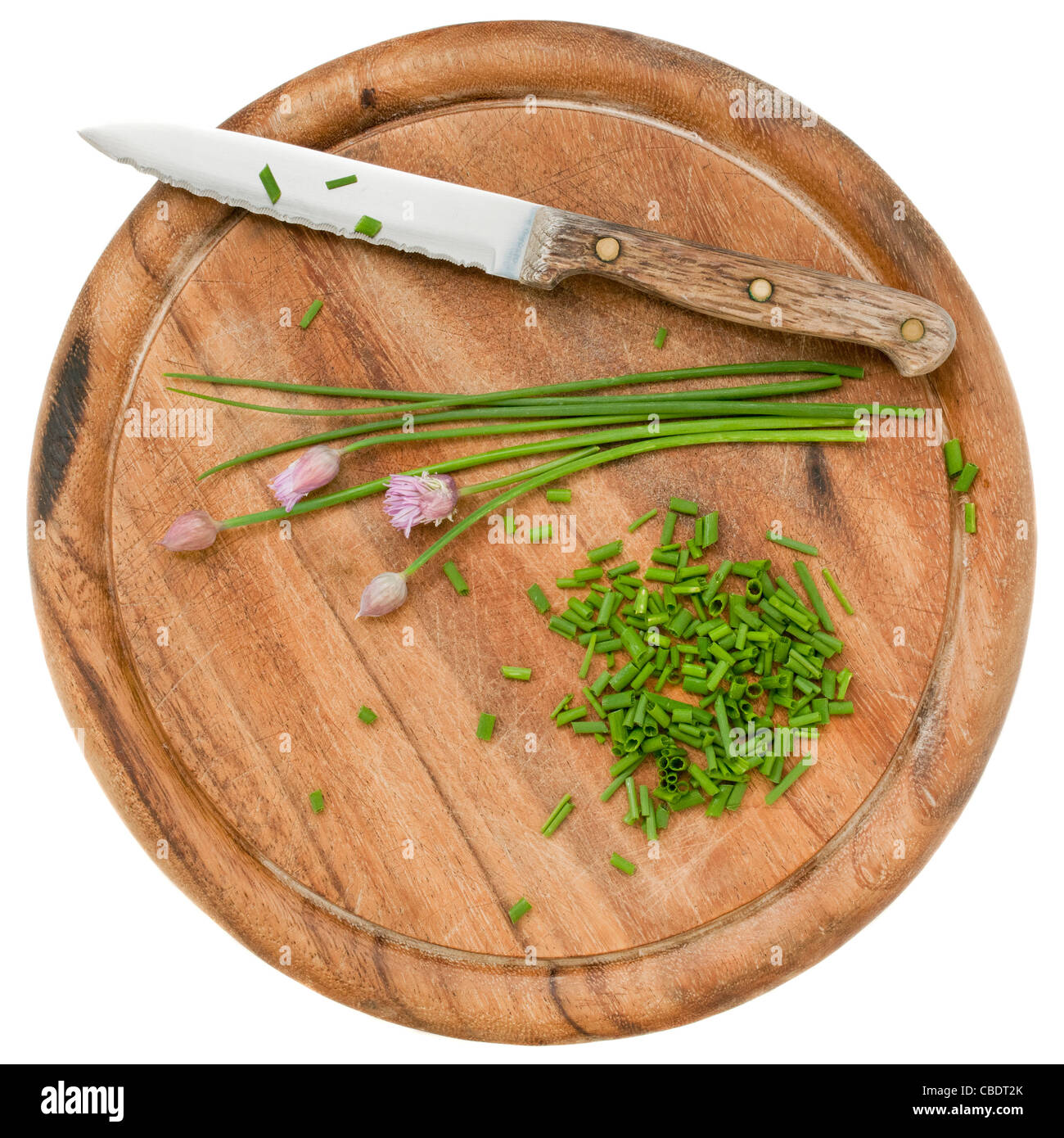 green chives with flowers chopped on a wood cutting board, isolated on white Stock Photo