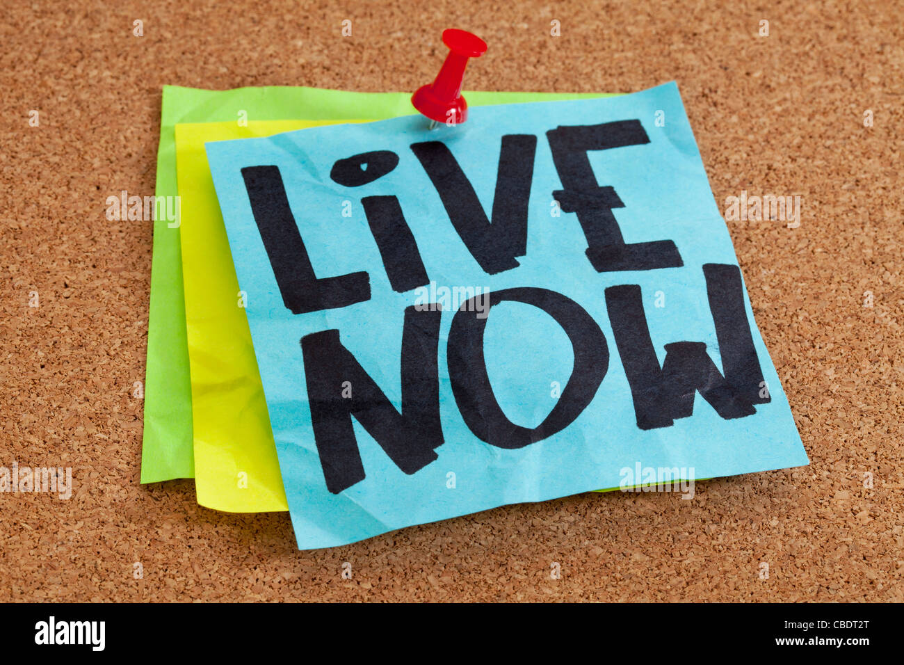 live now reminder on blue sticky note posted on cork board - Stock Image