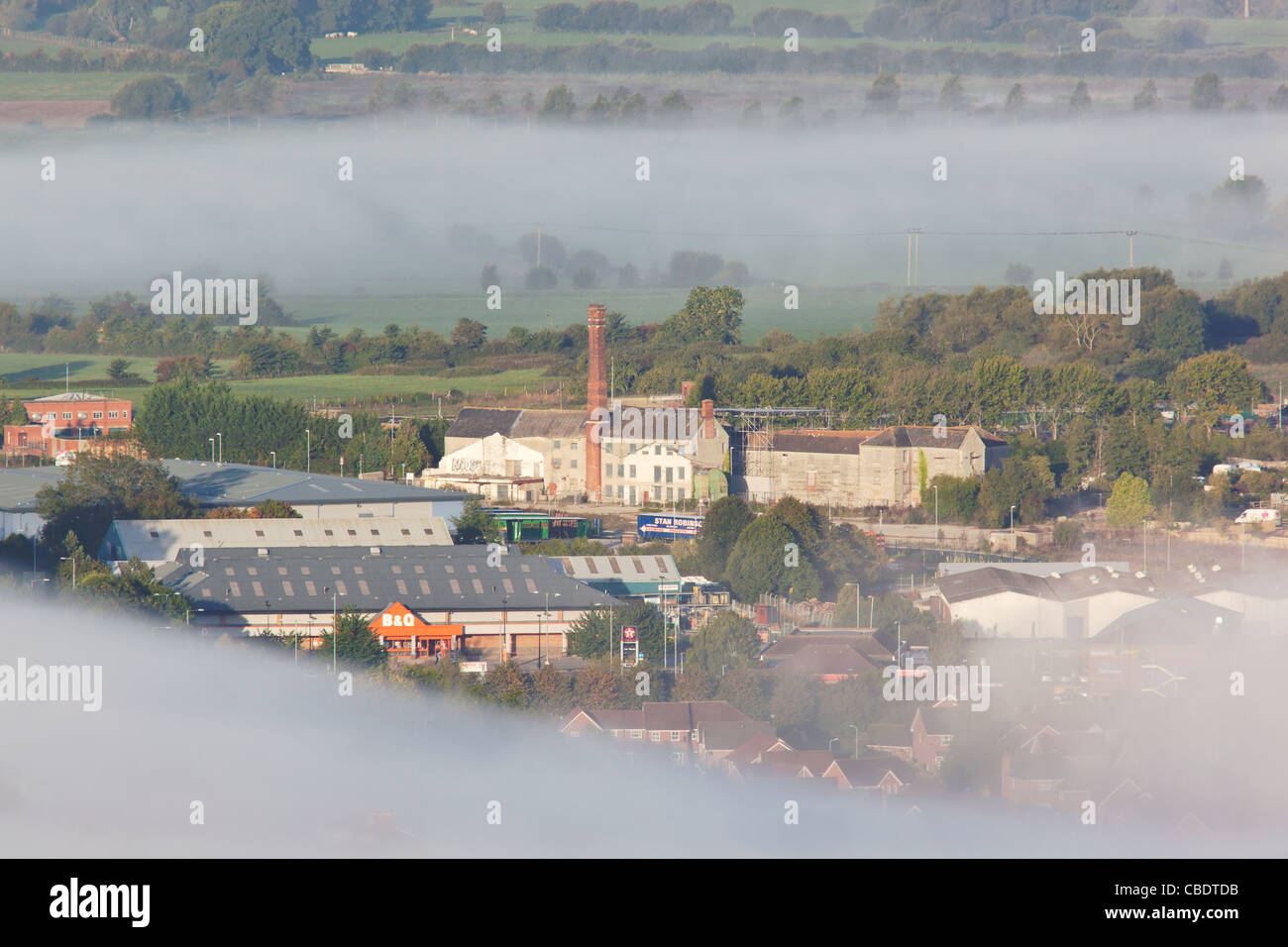 View of old factories near Glastonbury town surrounded by mist early morning from the summit of the Tor - Stock Image
