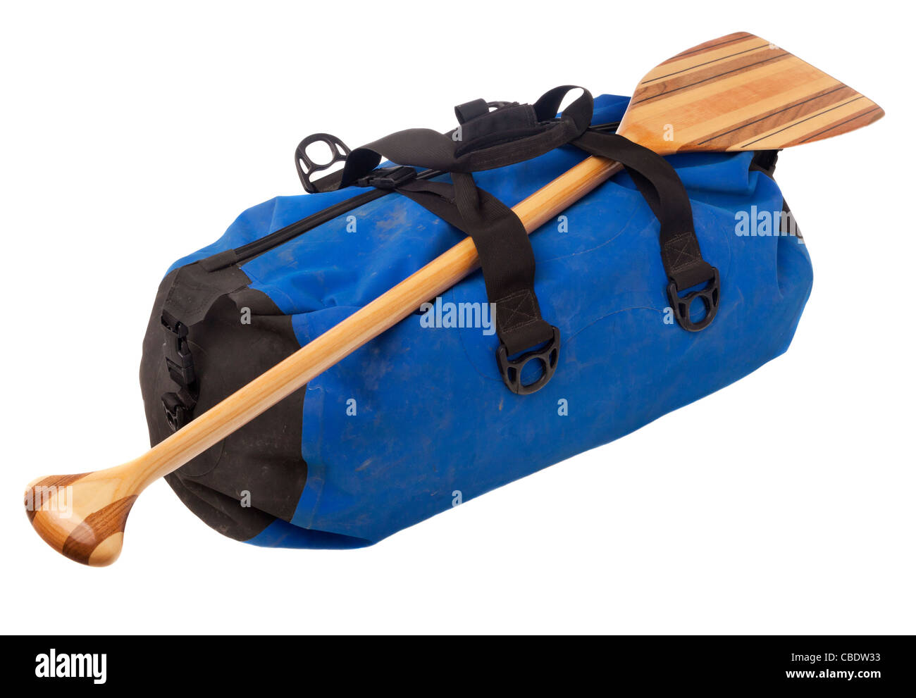 paddling trip or vacation concept - wooden canoe paddle and waterpoof duffel with river mud stains, isolated on - Stock Image