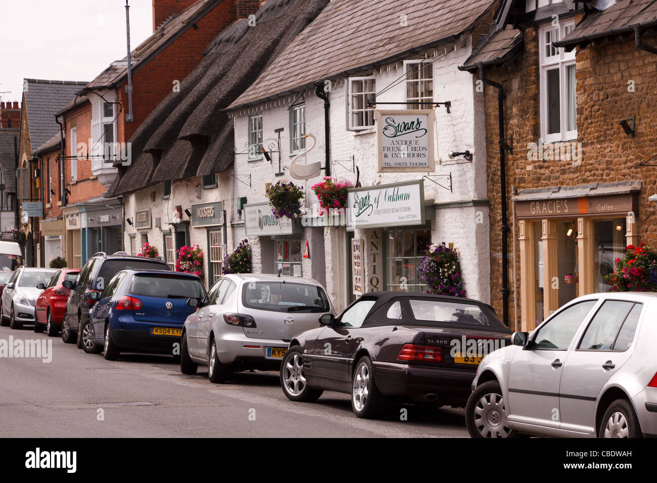 Old shop fronts, signs and parked cars along town centre shopping street, Mill street, Oakham, Rutland, England, - Stock Image
