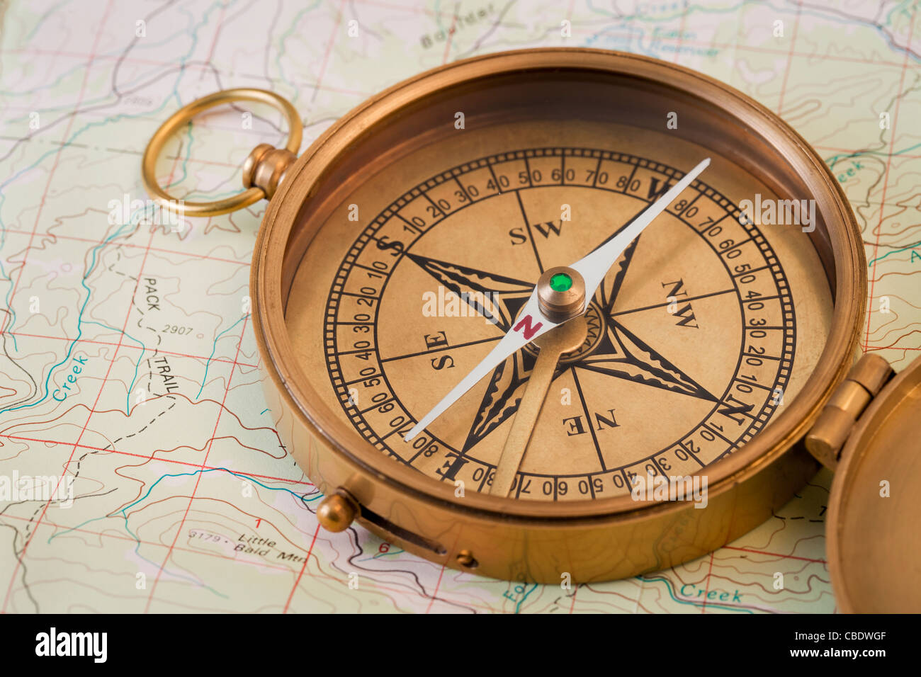 vintage pocket brass compass opened over topographical map - Stock Image