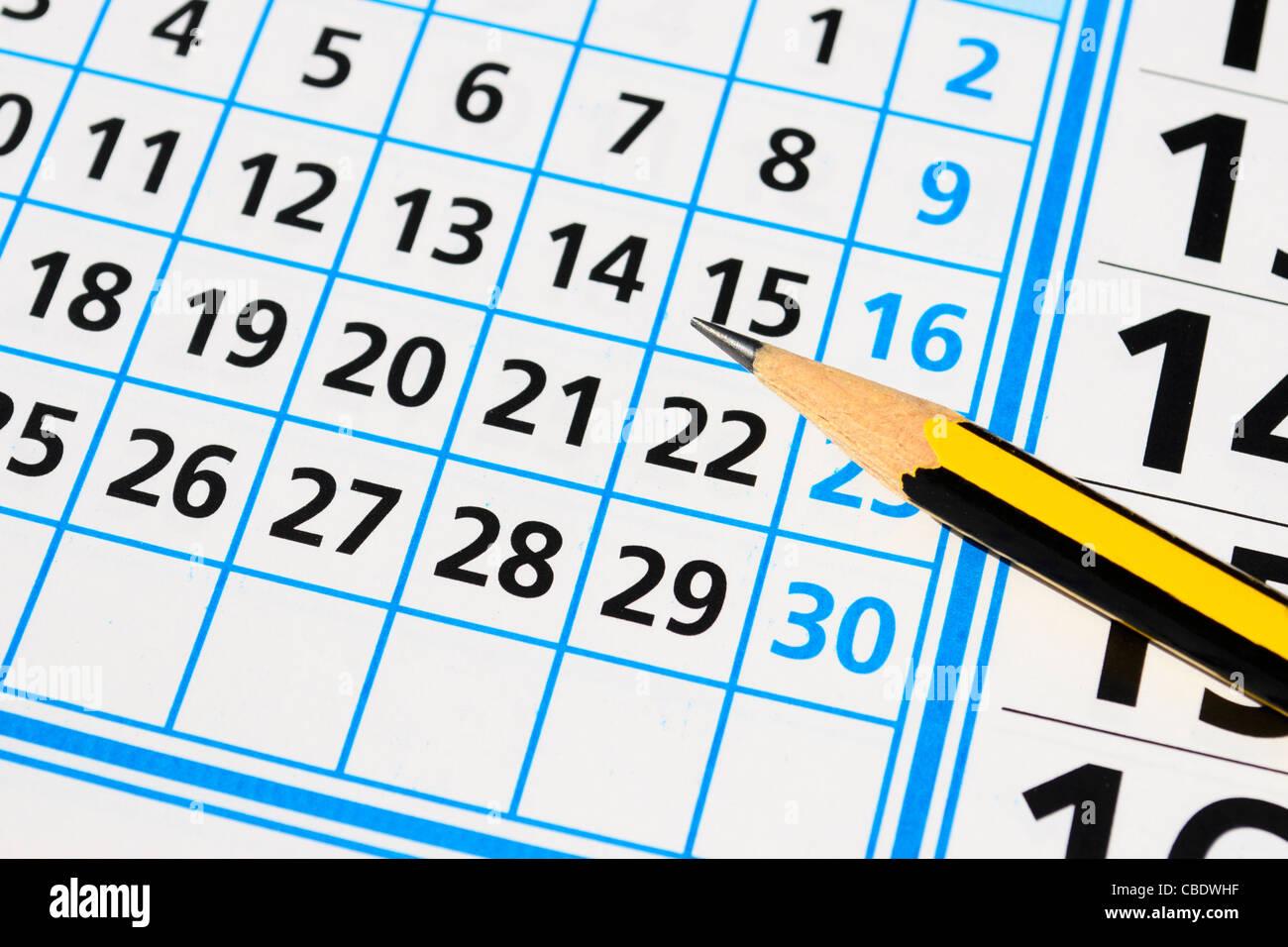 bi-color pencil on a calendar - Stock Image
