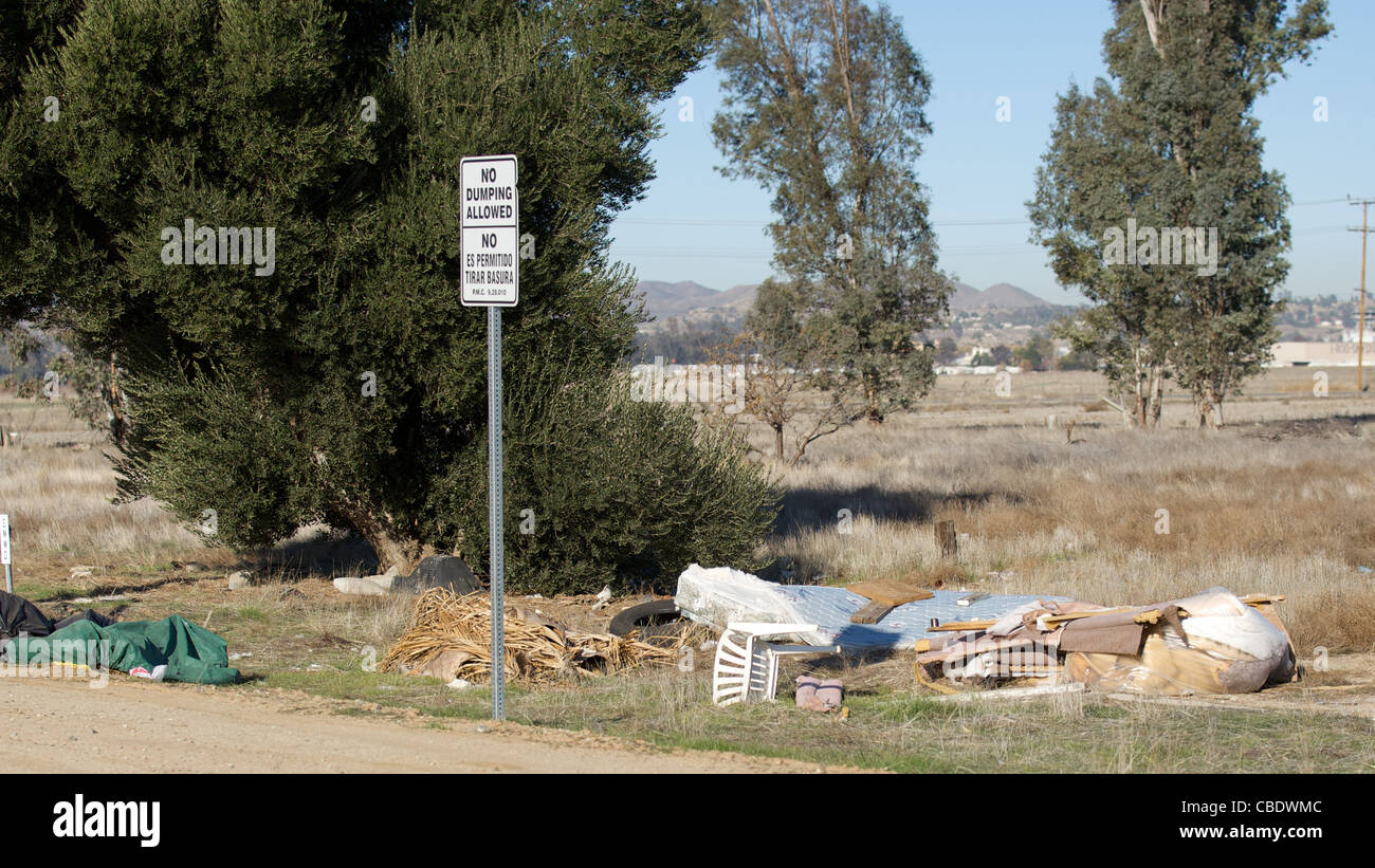 Trash alongside a dirt road next to a no dumping sign - Stock Image