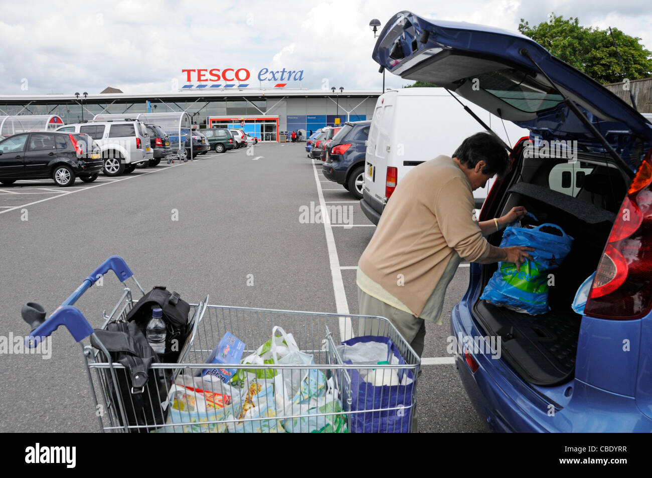Sixty nine year old senior woman pensioner loading weekly food shop from plastic bags in trolley into back of hatchback - Stock Image