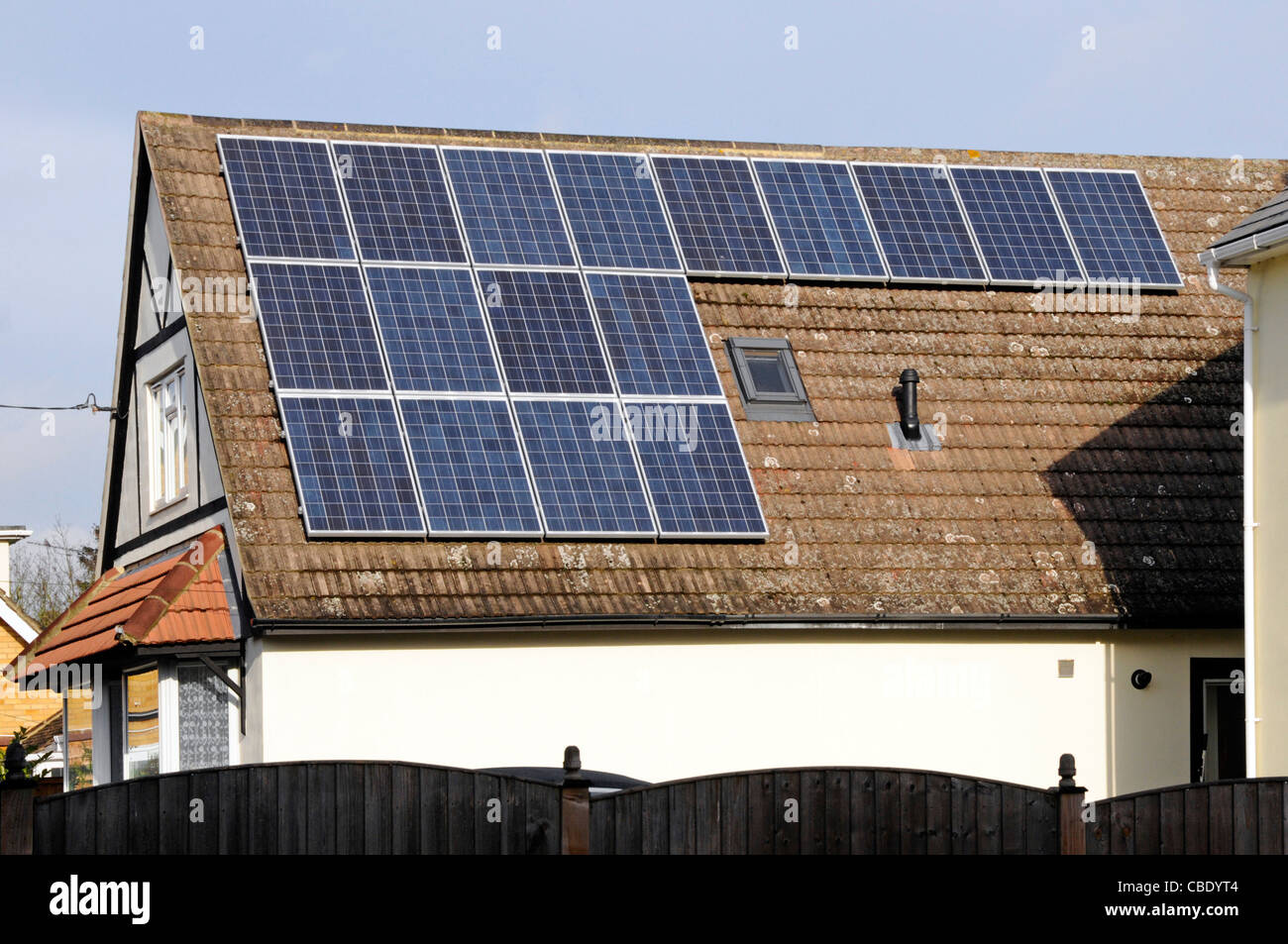 Solar Panels in sunshine installed on south facing roof on sunny blue sky day detached house alongside an existing - Stock Image