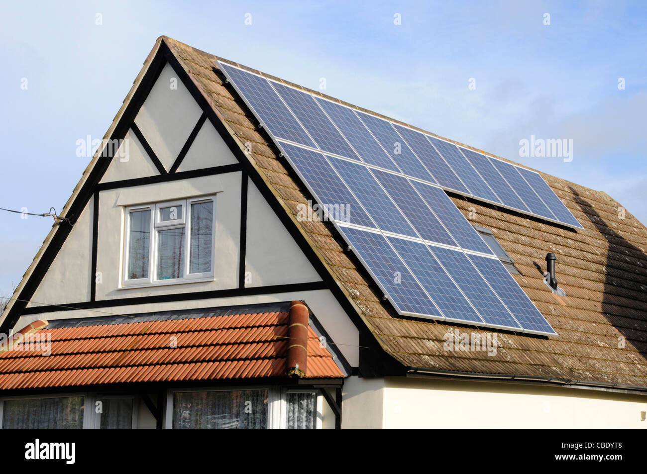 Solar Panels installed on roof of detached house alongside an existing rooflight - Stock Image