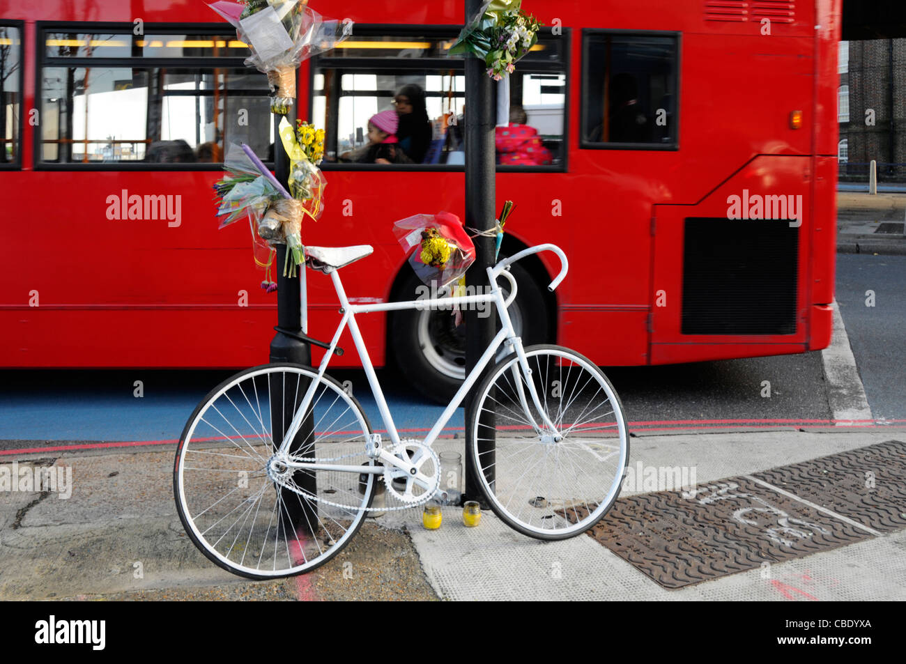 White push bike memorial and flowers for cyclist killed at road junction includes blue cycle lane road markings - Stock Image