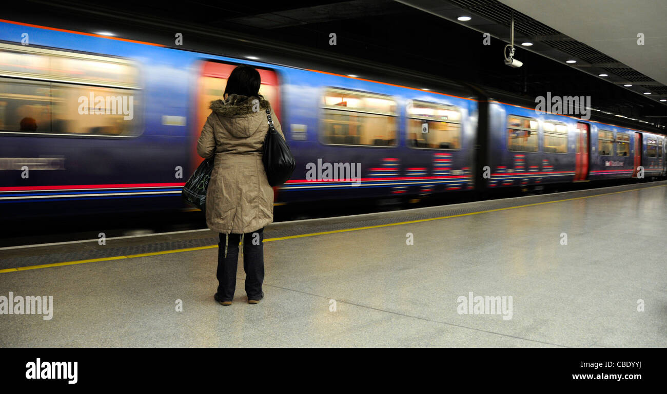 Woman standing alone on station platform with moving train beyond - Stock Image