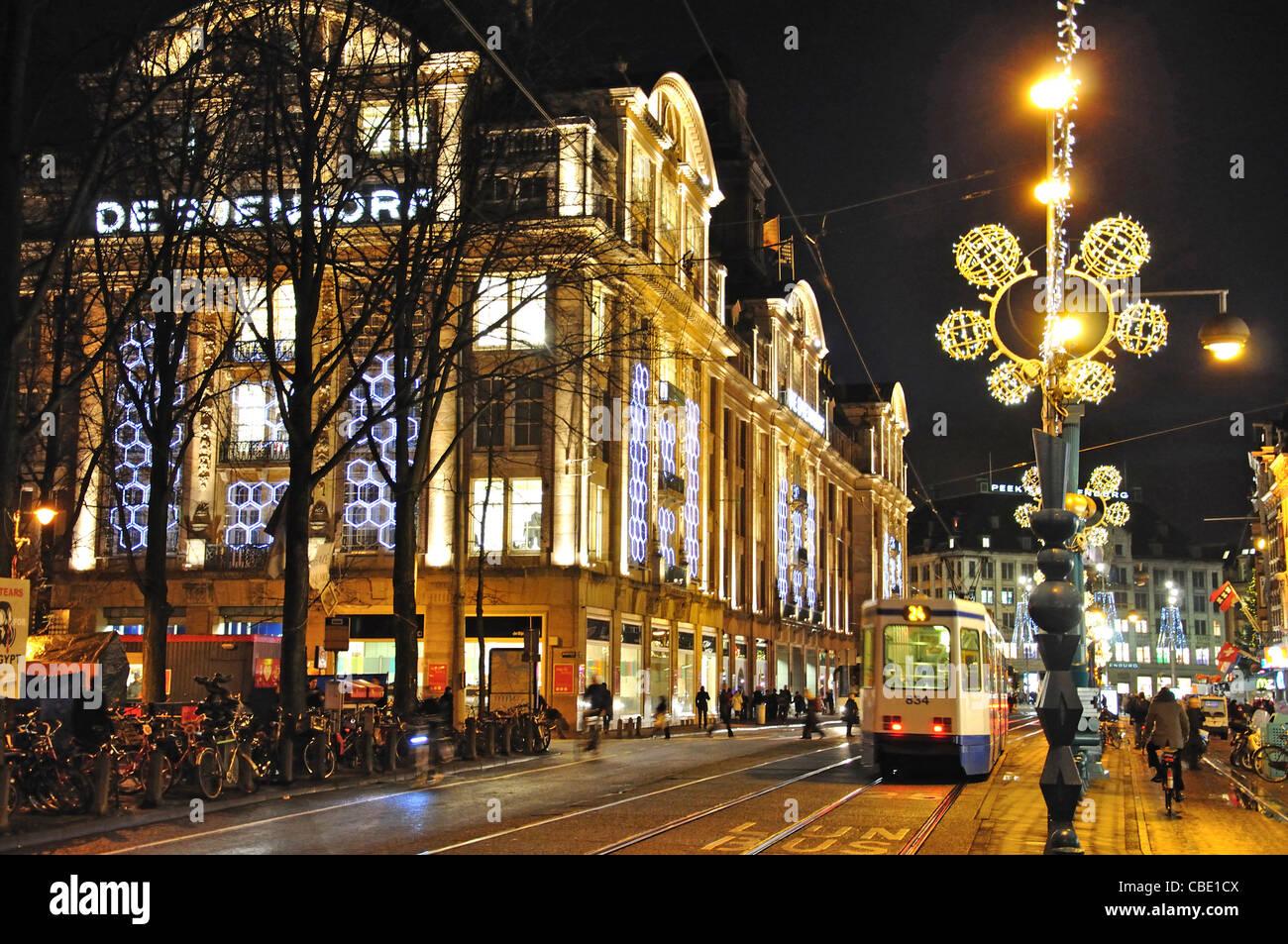 De Bijenkorf department store at night, Damrak, Amsterdam, Noord-Holland, Kingdom of the Netherlands - Stock Image
