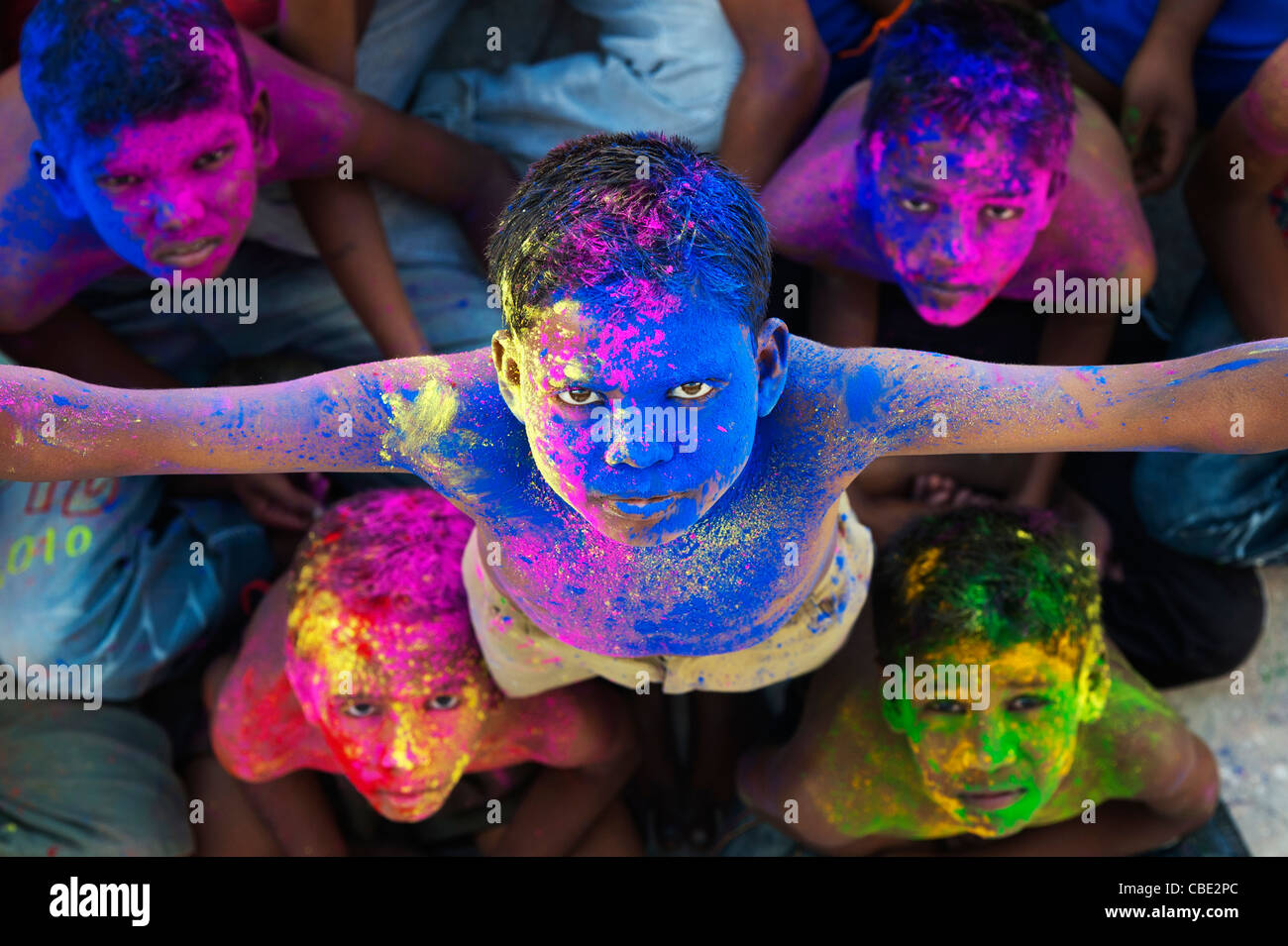 Young Indian boys covered in coloured powder pigment - Stock Image