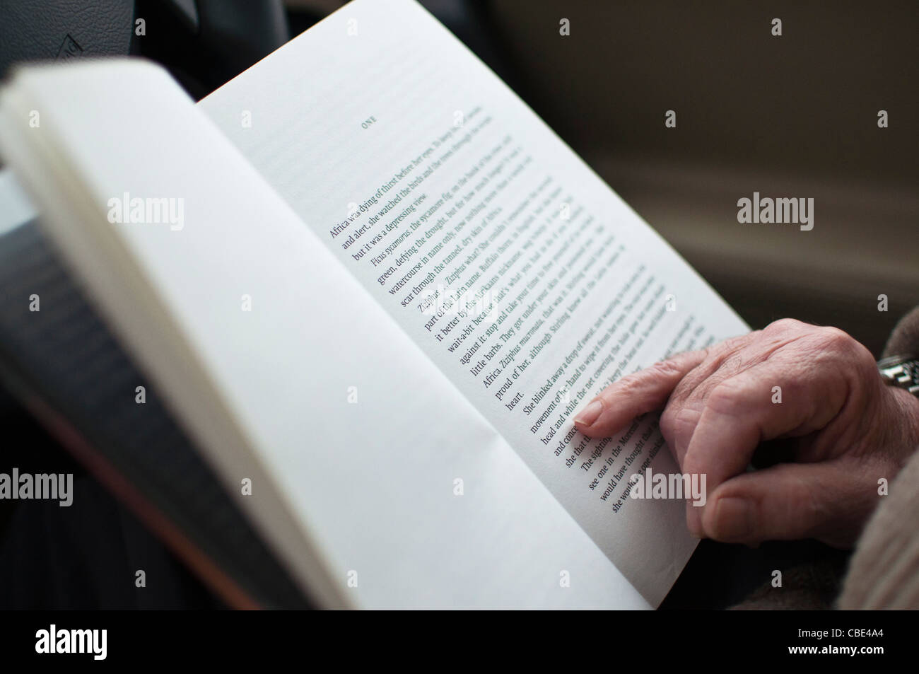Close Up of a Hand of a Male Tracing Text with Finger, Whilst Reading A Book. - Stock Image