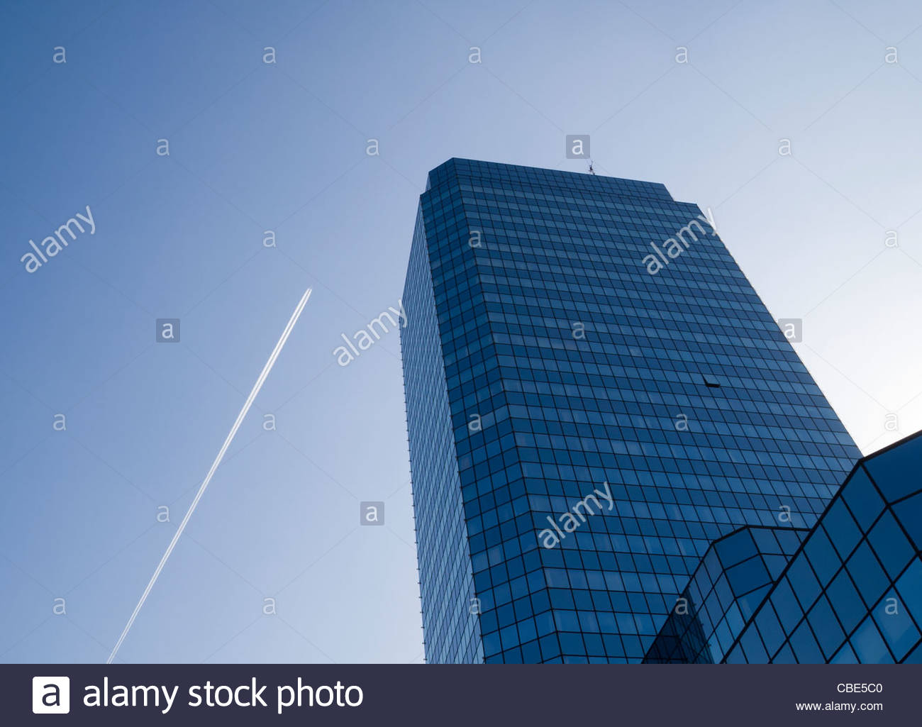 A blue glass office building pointing to the sky  while a jetliner passes by with a long trail - Stock Image