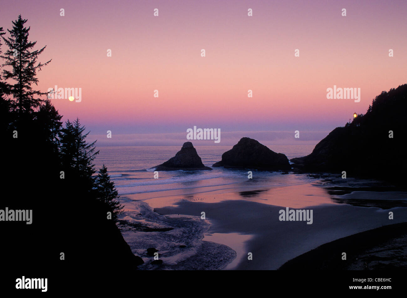 Heceta Head Lighthouse and full moon setting over ocean; Devils Elbow State Park, Oregon coast. - Stock Image