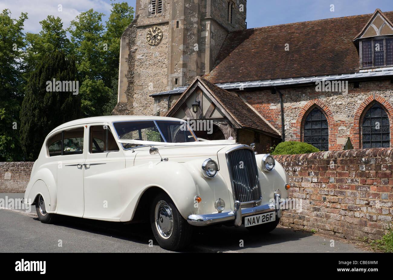 A stationary white wedding and bridal car waiting outside St John ...
