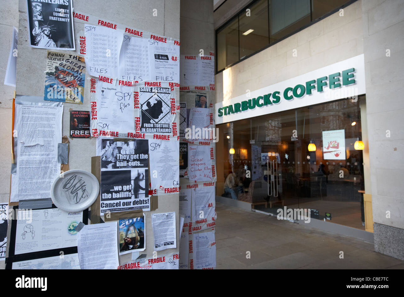 anti bailout and conspiracy occupy protest posters outside starbucks London England Uk United Kingdom - Stock Image