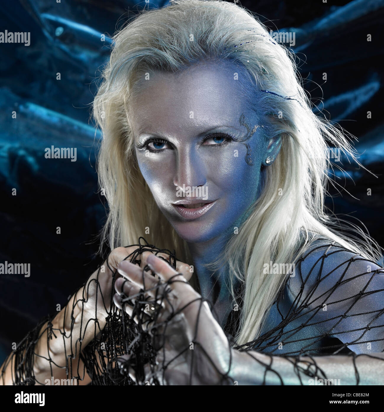 mystic mermaid theme showing the portrait of a bodypainted woman with black fishing net, studio photography in black - Stock Image