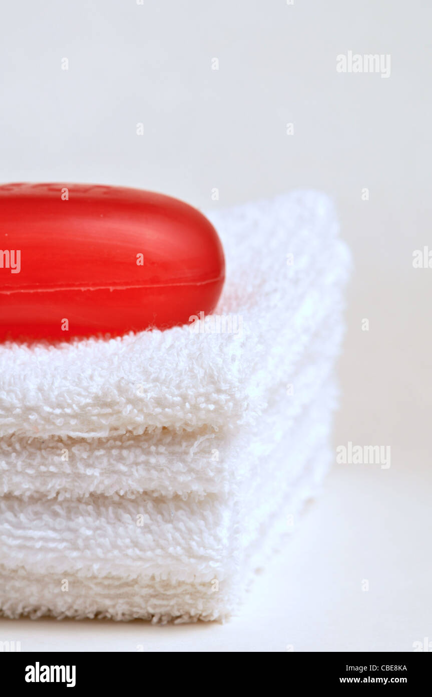 A bar of soap sits on top of a stack of wash clothes - Stock Image