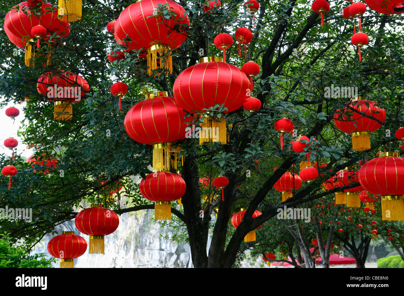 Red National Day lanterns in trees at Elephant Trunk Hill Park on Li River Guilin China - Stock Image