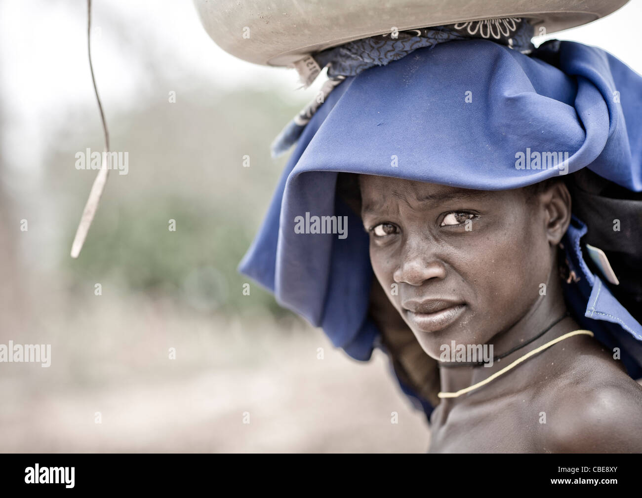 Mucubal Woman With Ompota Headdress Carrying A Basket On Her Head, Virie Area, Angola - Stock Image
