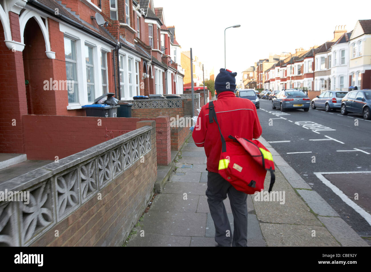 postman delivering mail on a cold december morning in cricklewood north london england united kingdom uk - Stock Image