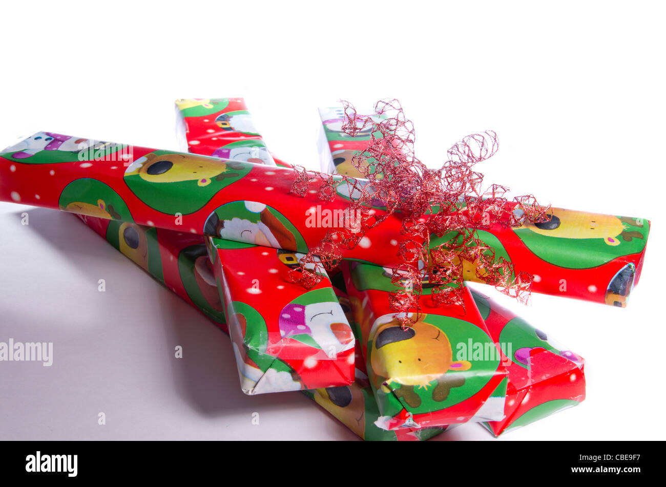 A Pile Of Christmas Gifts Wrapped In Festive Red Paper With Cartoon Reindeers On Them