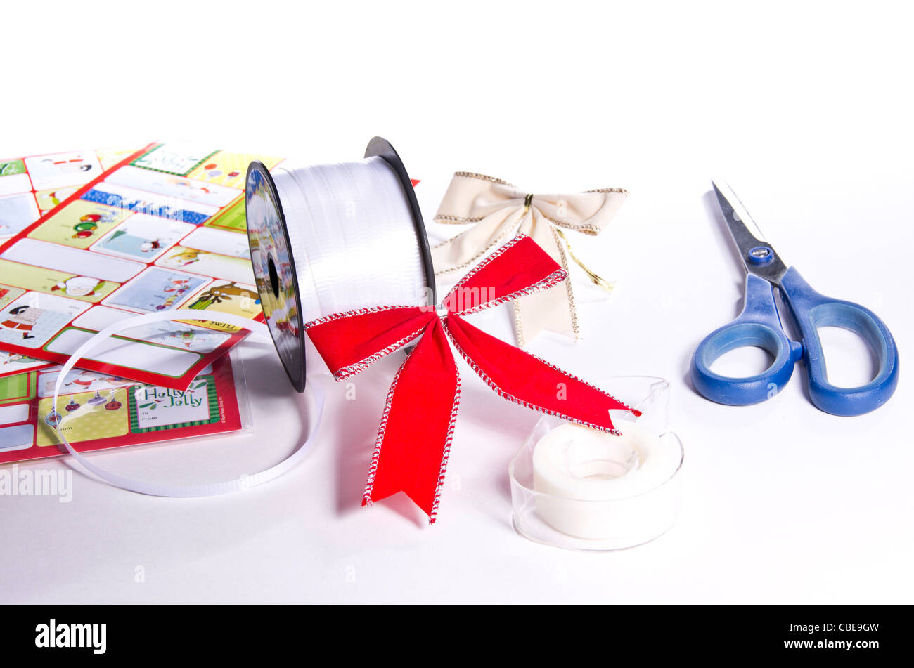 Various gift wrapping supplies including scissors, ribbon, tape, bows and gift tags. - Stock Image