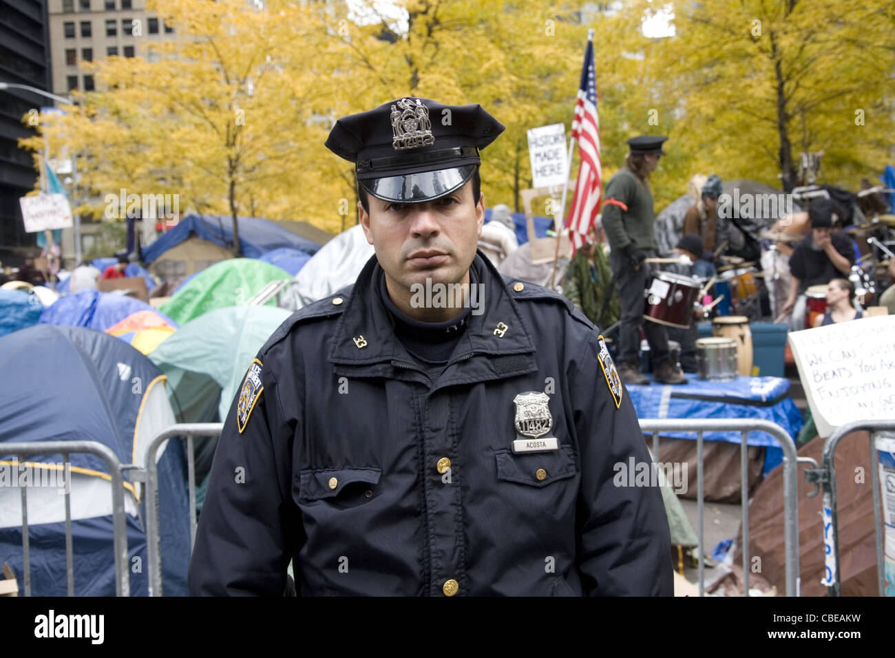 Serious looking NYPD officer at the Occupy Wall Street encampment in downtown Manhattan at Zuccotti Park, New York - Stock Image