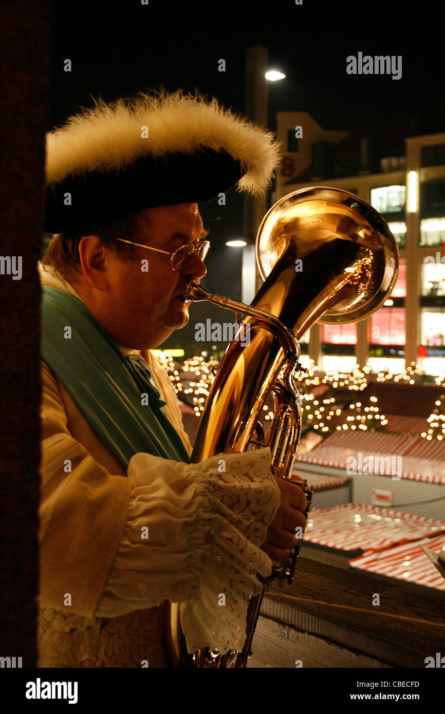 A local horn player with view on the Christmas market playing Christmas songs at the top of the city hall of Leipzig, - Stock Image