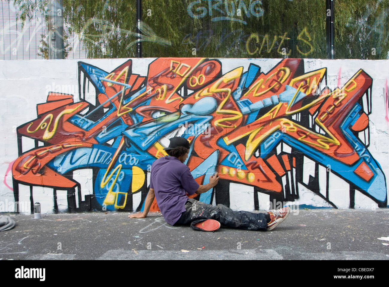 Teenage Boy Painting Abstract Graffiti Art Mural on Wall from Rear