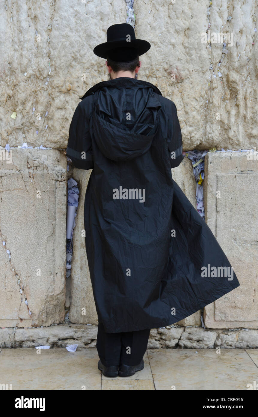 Orthodox Jew with raincoat praying at the Western Wall. Jerusalem Old City. israel - Stock Image