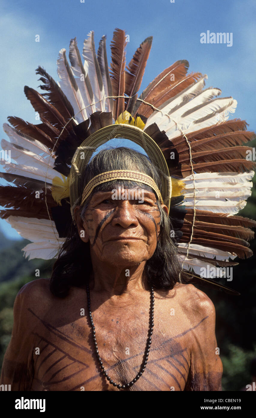 Brazil. Karaja Indian elder wearing traditional feather headdress, seed necklace and body paint. - Stock Image