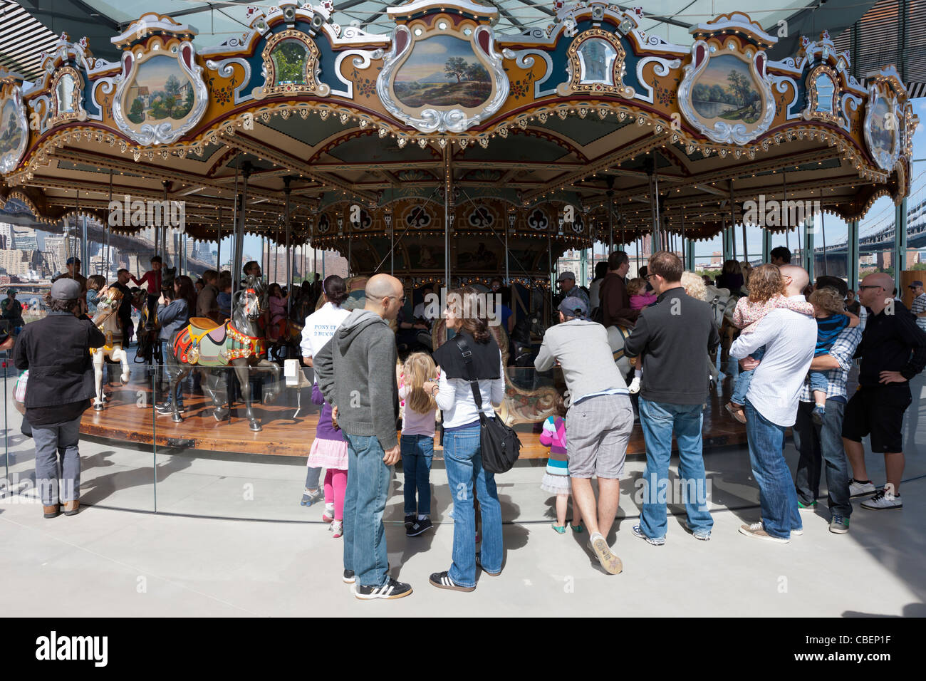People visit historic Jane's Carousel in Brooklyn Bridge Park in the DUMBO section of Brooklyn in New York City. - Stock Image