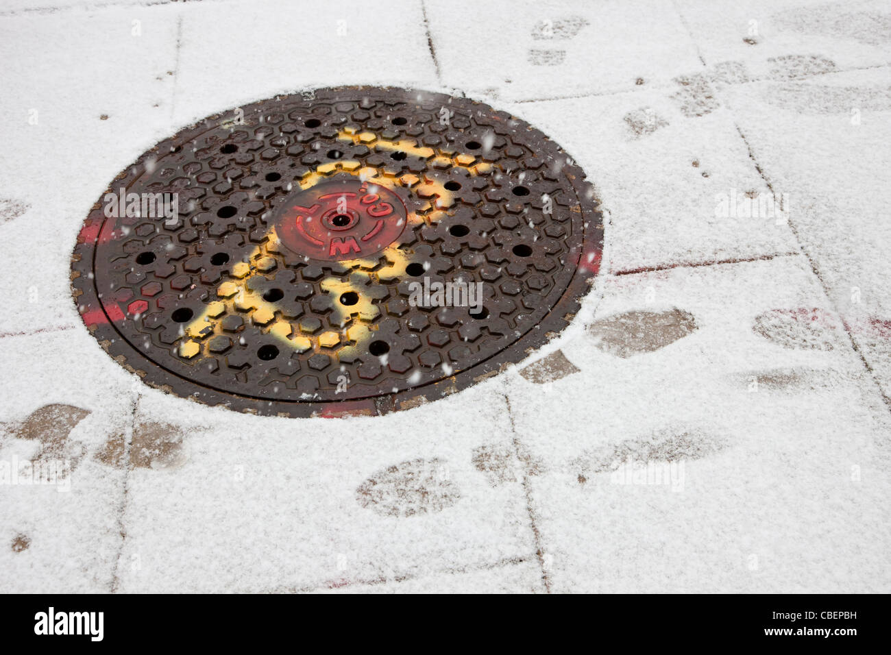A manhole cover on a snowy sidewalk in winter. - Stock Image