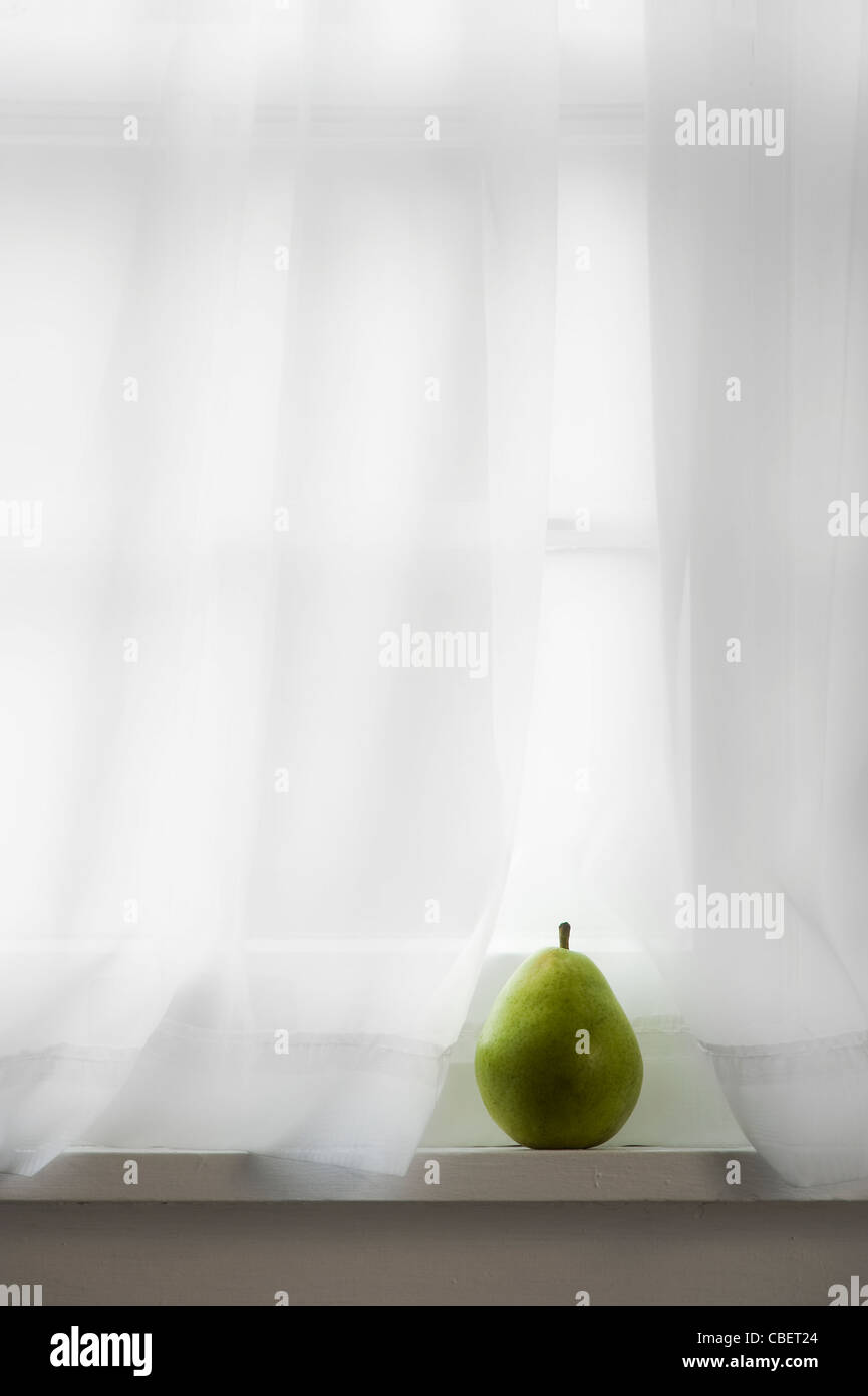 Pear On Window Sill With White Curtain Stock Photo