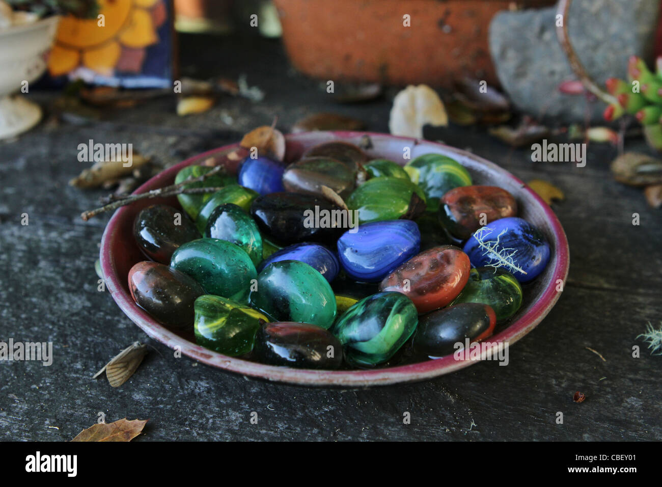 A bowl of colorful polished rocks. - Stock Image