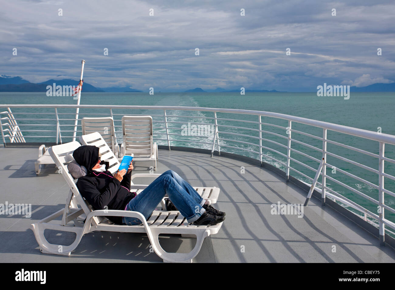 Woman reading on the ferry deck. Inside Passage. Alaska. USA - Stock Image