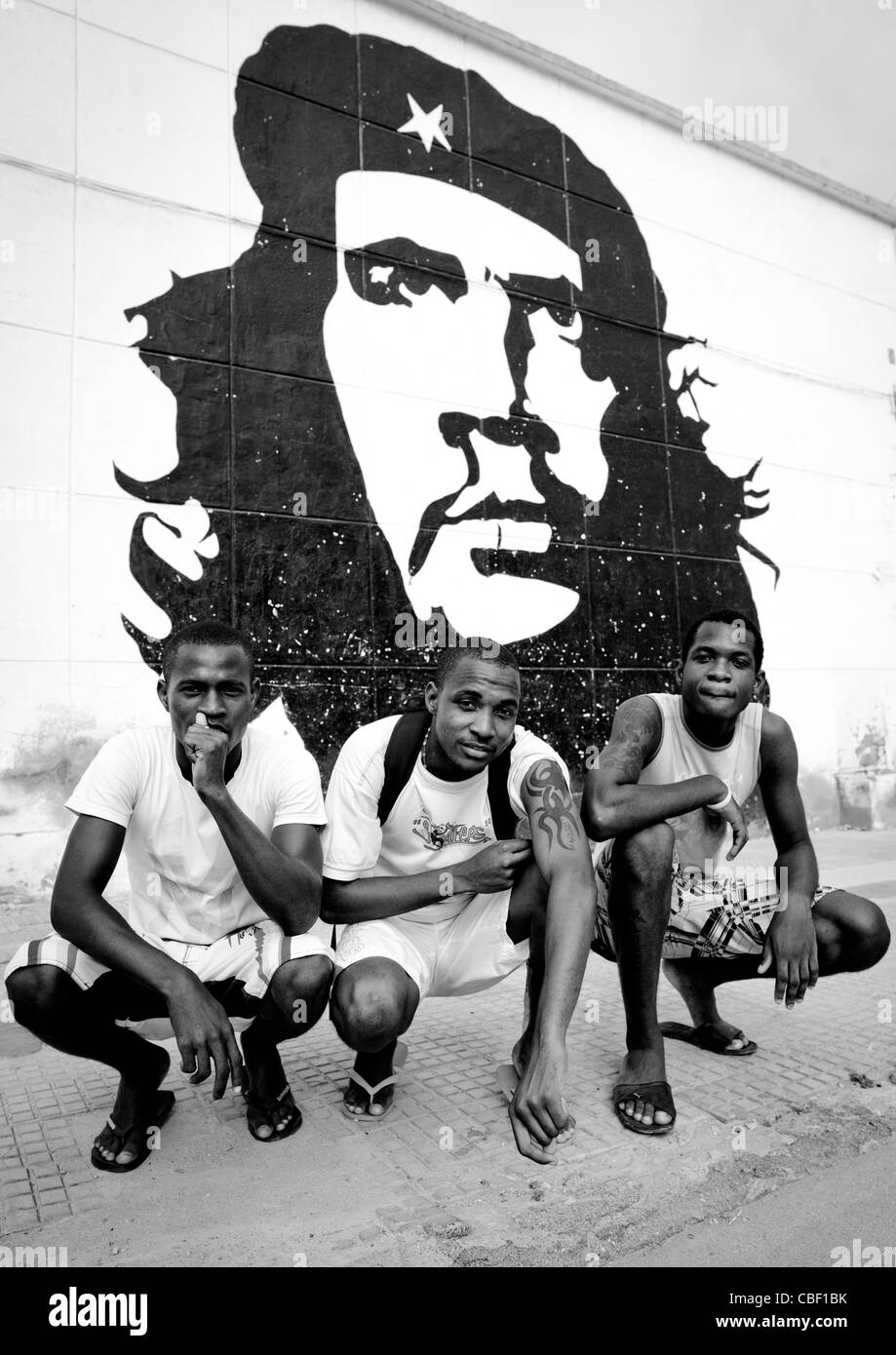 Men Crouched In Front Of A Che Guevara Wall Painting, Sumbe, Angola - Stock Image
