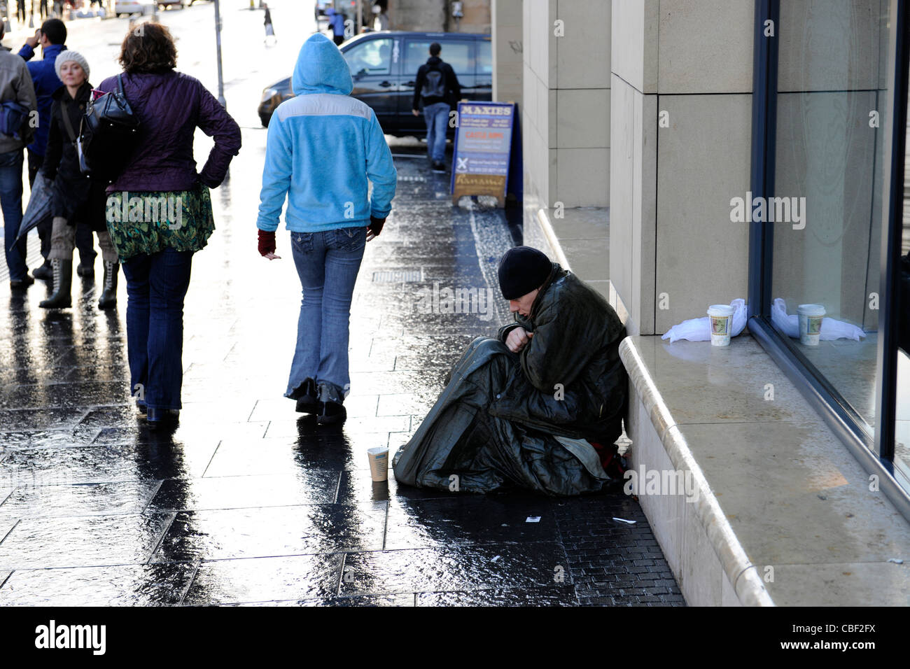 Homeless man shivers in rain while begging in Edinburgh, Scotland. - Stock Image