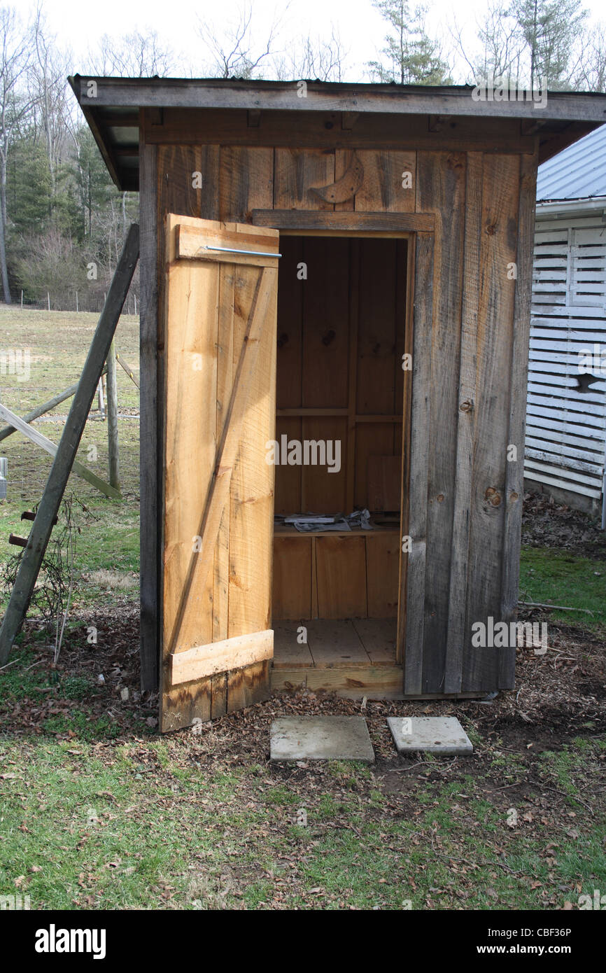 Country outhouse with door open - Stock Image
