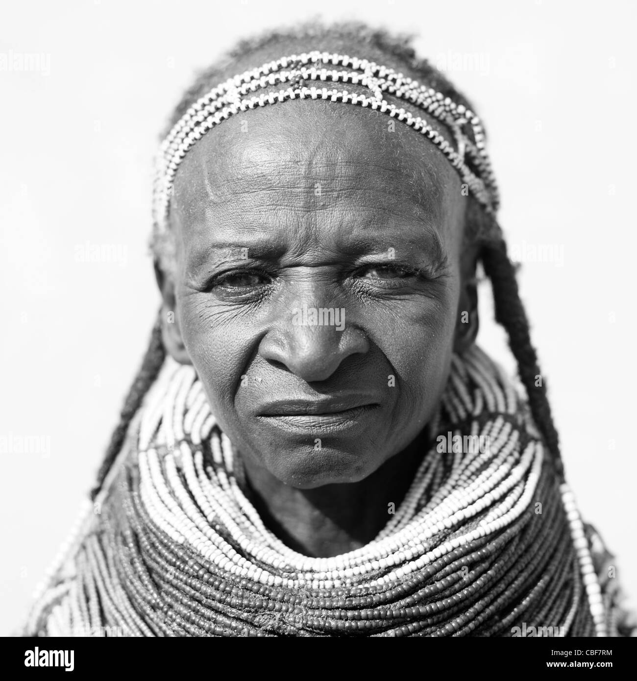 Old Mwila Woman With Vilanda Necklace And Traditional Hairstyle, Angola - Stock Image