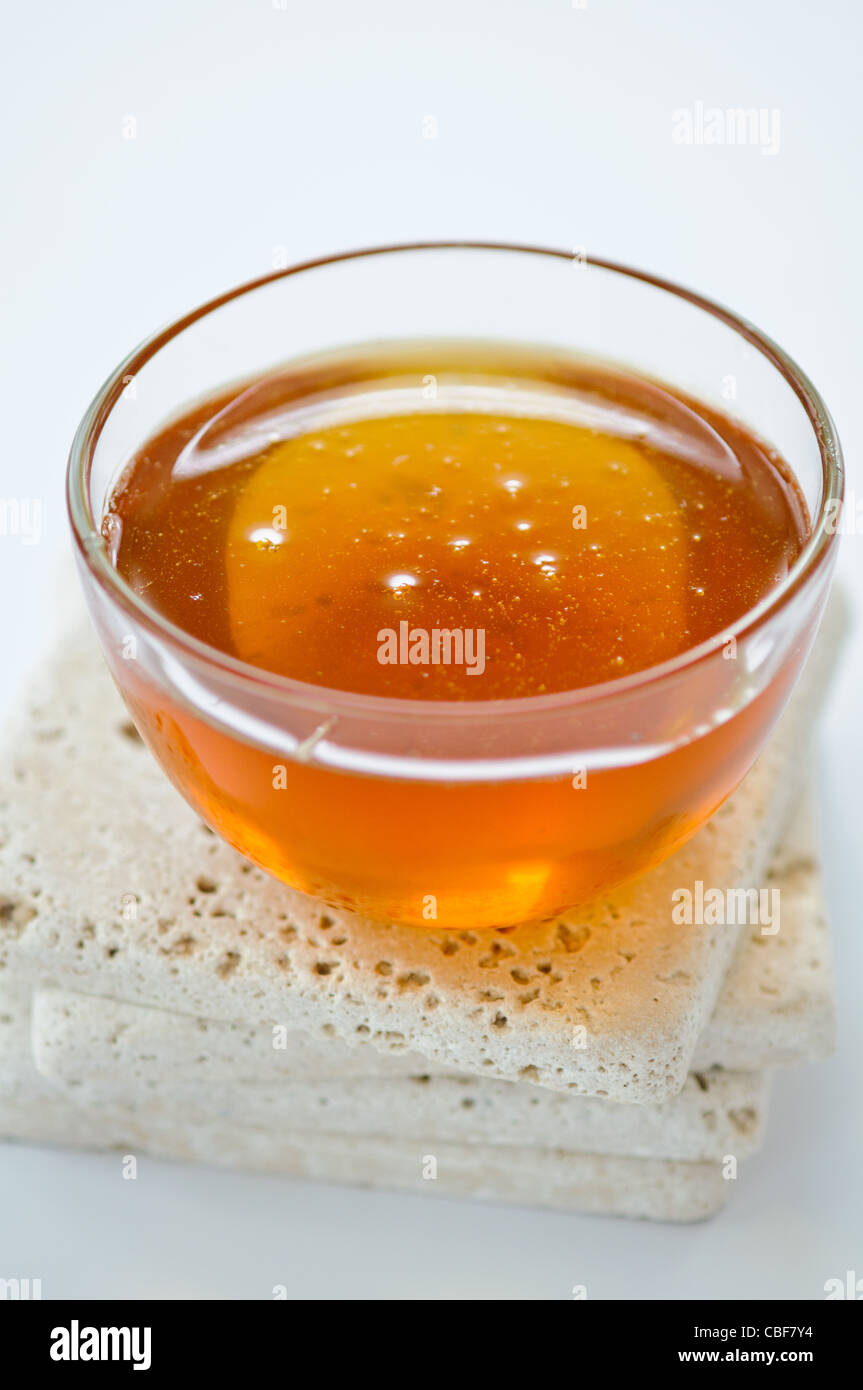 Glass bowl of runny honey - Stock Image