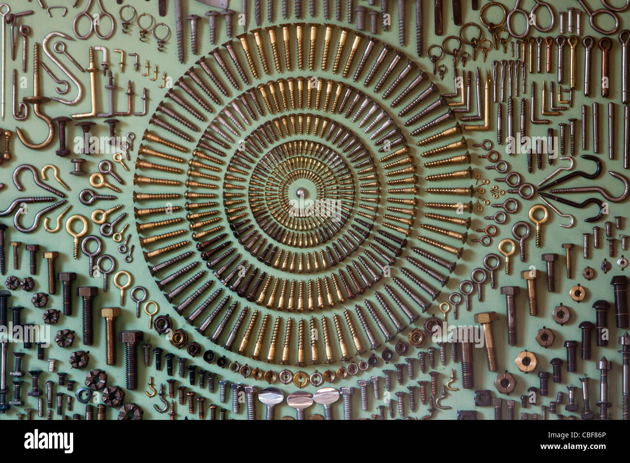 screws hooks eyes rivets nuts and bolts mounted in regular pattern on display board - Stock Image