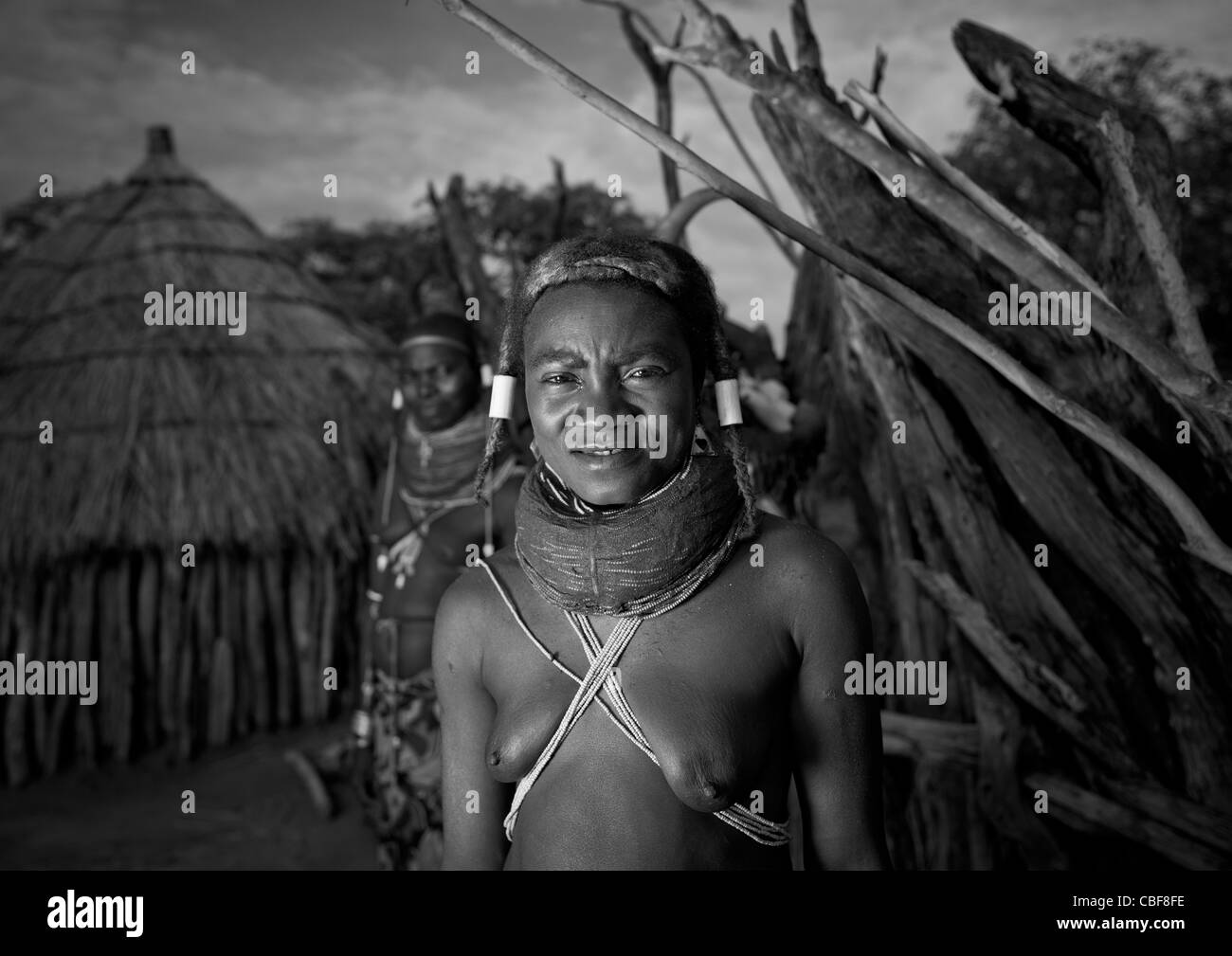 Mwila Woman With Vilanda Necklace In Front Of Her Hut, Chibia Area, Angola - Stock Image