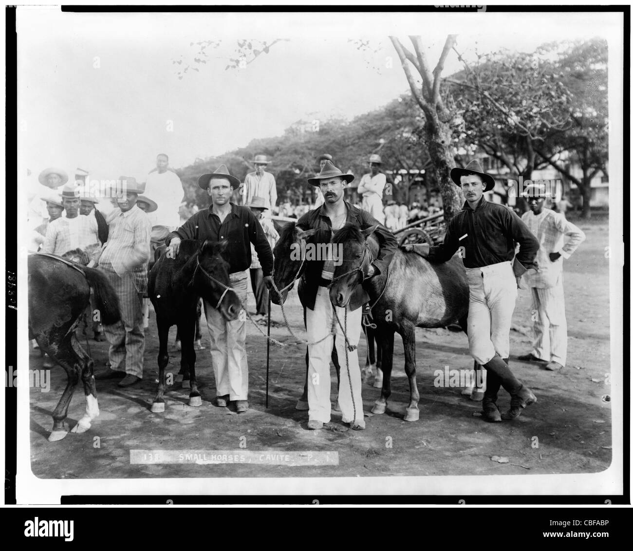 Three American soldiers(?), with small horses, and several Filipino men, Cavite, Philippine Islands. - Stock Image