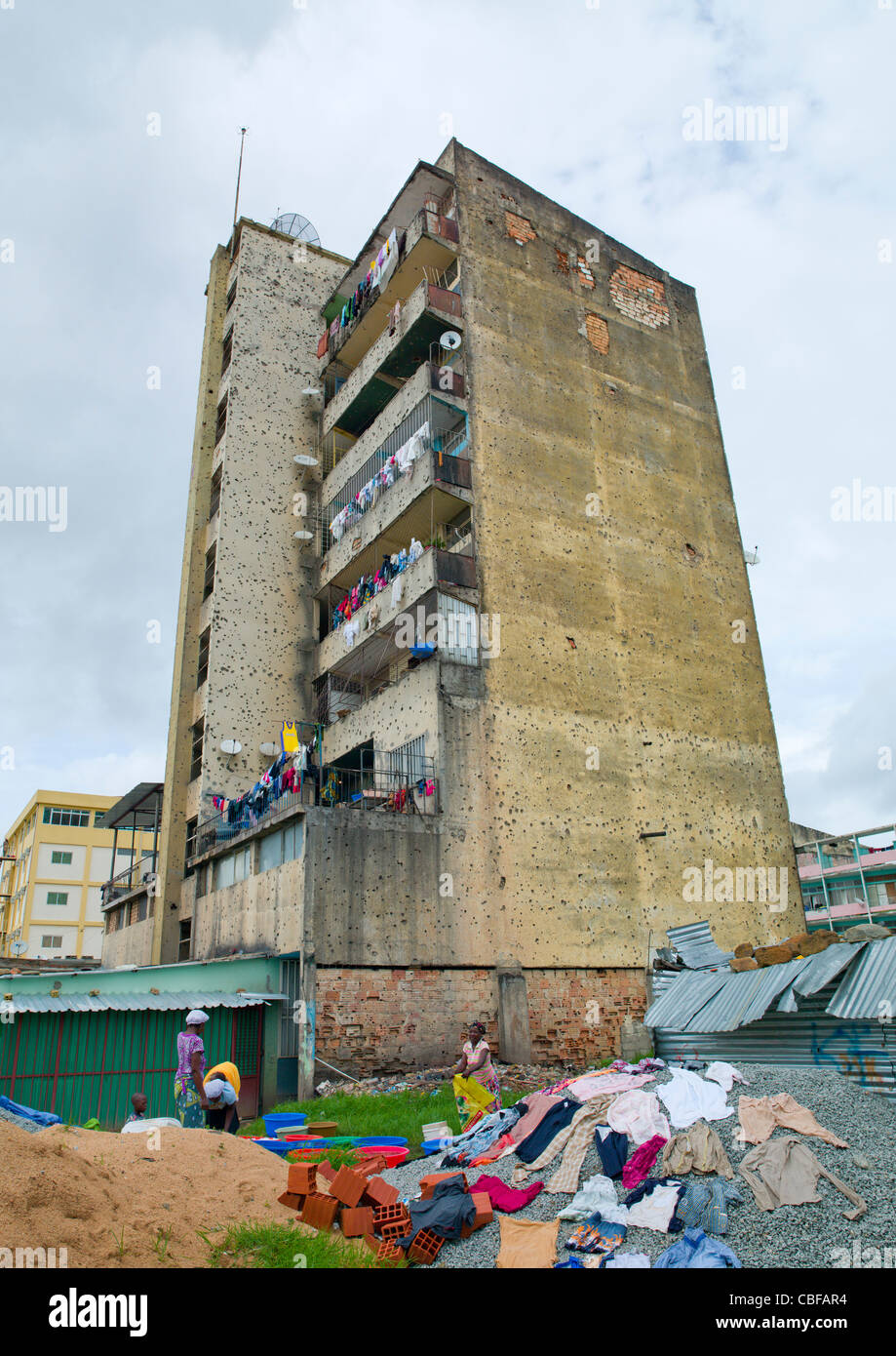 Women Doing Their Laundry At The bottom Of Their Building Riddled With Bullet Impacts From Civil War, Huambo, Angola - Stock Image